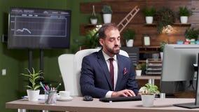 Hombre de negocios temprano en el trabajo solamente en los tipos de la oficina en el ordenador almacen de metraje de vídeo