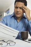 Hombre de negocios tensado Reading Document Imagen de archivo