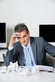 Hombre de negocios tensado Sitting At Desk foto de archivo libre de regalías
