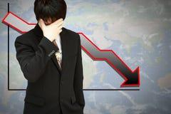 Hombre de negocios tensionado con el gráfico financiero inferior Imagen de archivo