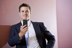 Hombre de negocios texting en vestíbulo Foto de archivo libre de regalías