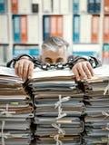 Hombre de negocios trabajado demasiado encadenado al lugar de trabajo imágenes de archivo libres de regalías