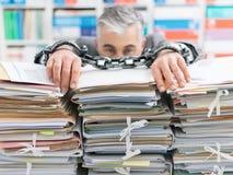 Hombre de negocios trabajado demasiado encadenado al lugar de trabajo imagen de archivo libre de regalías