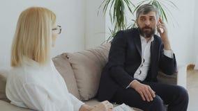 Hombre de negocios trastornado que habla de sus problemas con el psicólogo de sexo femenino metrajes