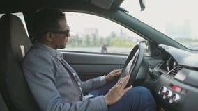 Hombre de negocios trastornado y enojado de la raza mixta que se sienta dentro de su coche al aire libre