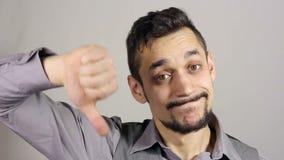Hombre de negocios triste con una barba que muestra los pulgares abajo metrajes