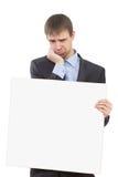 Hombre de negocios triste que lleva a cabo un espacio en blanco blanco fotografía de archivo