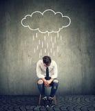 Hombre de negocios triste que se sienta en una silla que mira abajo con una nube de lluvia sobre él Fotos de archivo libres de regalías