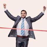 Hombre de negocios triunfante delante de la cinta que comienza fotos de archivo