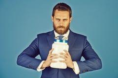 Hombre de negocios u hombre barbudo con el tarro pl?stico en fondo azul fotos de archivo