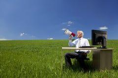 Hombre de negocios usando el megáfono en un campo Foto de archivo libre de regalías