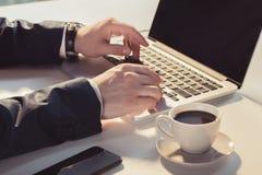 Hombre de negocios usando el ordenador portátil con la pantalla en blanco mientras que se sienta en la tabla Imagen de archivo libre de regalías
