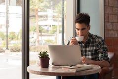 Hombre de negocios usando el ordenador portátil con la tableta y pluma en la tabla de madera Fotos de archivo libres de regalías