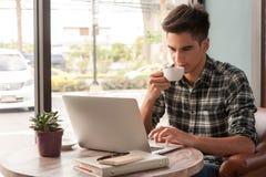 Hombre de negocios usando el ordenador portátil con la tableta y pluma en la tabla de madera Fotos de archivo