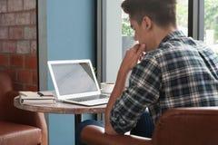 Hombre de negocios usando el ordenador portátil con la tableta y pluma en la tabla de madera Foto de archivo libre de regalías