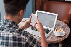 Hombre de negocios usando el ordenador portátil con la tableta y pluma en la tabla de madera adentro Imagen de archivo libre de regalías