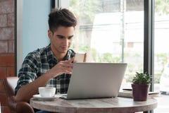 Hombre de negocios usando el ordenador portátil con la tableta y pluma en la tabla de madera adentro Imagenes de archivo