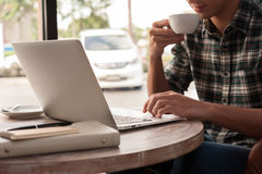 Hombre de negocios usando el ordenador portátil con la tableta y pluma en la tabla de madera adentro Foto de archivo libre de regalías