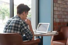 Hombre de negocios usando el ordenador portátil con la tableta y pluma en la tabla de madera adentro Fotos de archivo libres de regalías