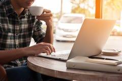 Hombre de negocios usando el ordenador portátil con la tableta y pluma en la tabla de madera adentro Fotografía de archivo