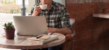 Hombre de negocios usando el ordenador portátil con la tableta y pluma en la tabla de madera adentro Fotografía de archivo libre de regalías