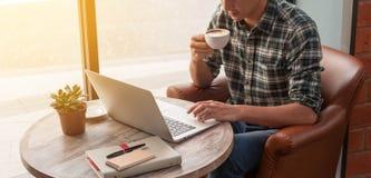 Hombre de negocios usando el ordenador portátil con la tableta y pluma en la tabla de madera adentro Foto de archivo