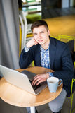 Hombre de negocios usando el ordenador portátil con la tableta y pluma en la tabla de madera en cafetería con una taza de opinión Fotografía de archivo libre de regalías