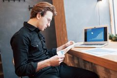 Hombre de negocios usando el ordenador portátil con la tableta y pluma en la tabla de madera en cafetería con una taza de café Un Imagen de archivo