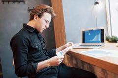 Hombre de negocios usando el ordenador portátil con la tableta y pluma en la tabla de madera en cafetería con una taza de café Un Imagenes de archivo