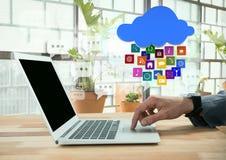 Hombre de negocios usando el ordenador portátil con los iconos de los apps por las ventanas brillantes con las plantas Fotografía de archivo libre de regalías