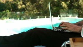 Hombre de negocios usando el ordenador portátil en deckchair almacen de video