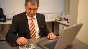 Hombre de negocios usando el ordenador portátil en la oficina, calculando almacen de metraje de vídeo