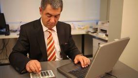 Hombre de negocios usando el ordenador portátil en la oficina, calculando metrajes