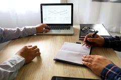 Hombre de negocios usando el ordenador portátil a enseñar y el análisis la situación encendido imagen de archivo