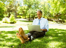 Hombre de negocios usando el ordenador portátil mientras que se relaja en parque Fotografía de archivo libre de regalías