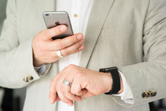 Hombre de negocios usando el reloj de Apple y Apple Imagen de archivo