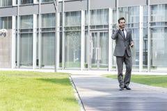 Hombre de negocios usando el teléfono celular mientras que camina en la trayectoria fuera de la oficina imagen de archivo libre de regalías