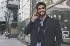 Hombre de negocios usando el teléfono elegante al aire libre Imagen de archivo libre de regalías