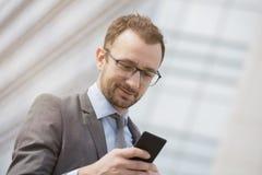 Hombre de negocios usando el teléfono elegante delante del negocio de cristal azul Imagenes de archivo