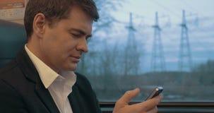 Hombre de negocios usando el teléfono elegante durante viaje en tren metrajes