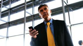 Hombre de negocios usando el teléfono móvil almacen de metraje de vídeo
