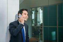 Hombre de negocios usando el teléfono móvil app que manda un SMS fuera de oficina en ciudad urbana con los edificios de los rasca Fotografía de archivo libre de regalías