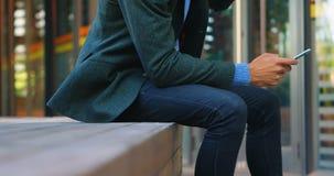 Hombre de negocios usando el teléfono móvil mientras que comiendo el café 4k almacen de metraje de vídeo