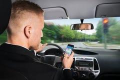 Hombre de negocios usando el teléfono móvil mientras que conduce un coche foto de archivo libre de regalías