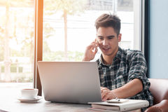 Hombre de negocios usando el teléfono móvil mientras que ordenador portátil del lookingat en de madera Imagen de archivo libre de regalías