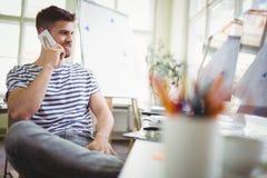 Hombre de negocios usando el teléfono móvil mientras que se sienta en oficina creativa Imagen de archivo