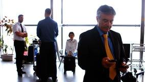 Hombre de negocios usando el teléfono móvil mientras que viajeros que obran recíprocamente con uno a almacen de video