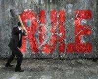 Hombre de negocios usando la almádena que agrieta palabra roja de la regla roto Fotografía de archivo