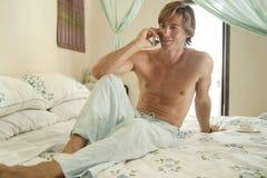 Hombre de negocios usando la célula en dormitorio Foto de archivo