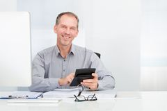 Hombre de negocios usando la calculadora Imagen de archivo